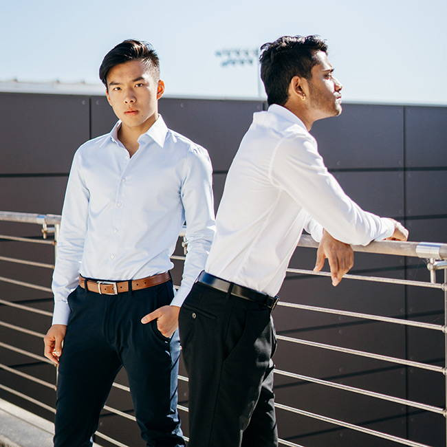 asian men wearing slim dress shirts looking over balcony