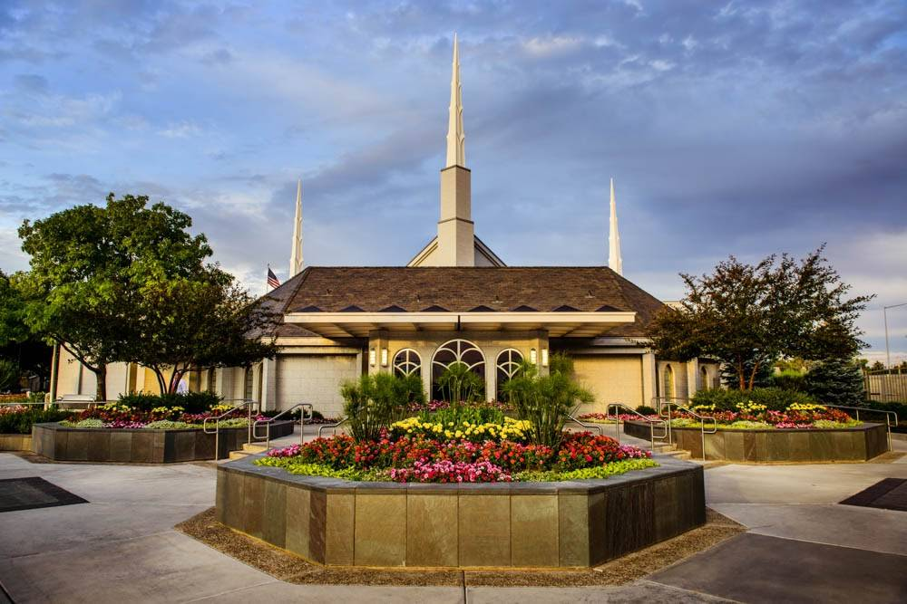 Boise Idaho Temple against a blue sky. A large flowerbed stands in the center.