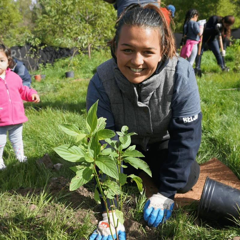 On voit une femme en train de replanter un arbre qui a un geste écologique en rapport à l'éthique.