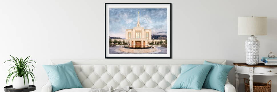 Framed Ogden Temple photo on the wall above a whitei sofa.