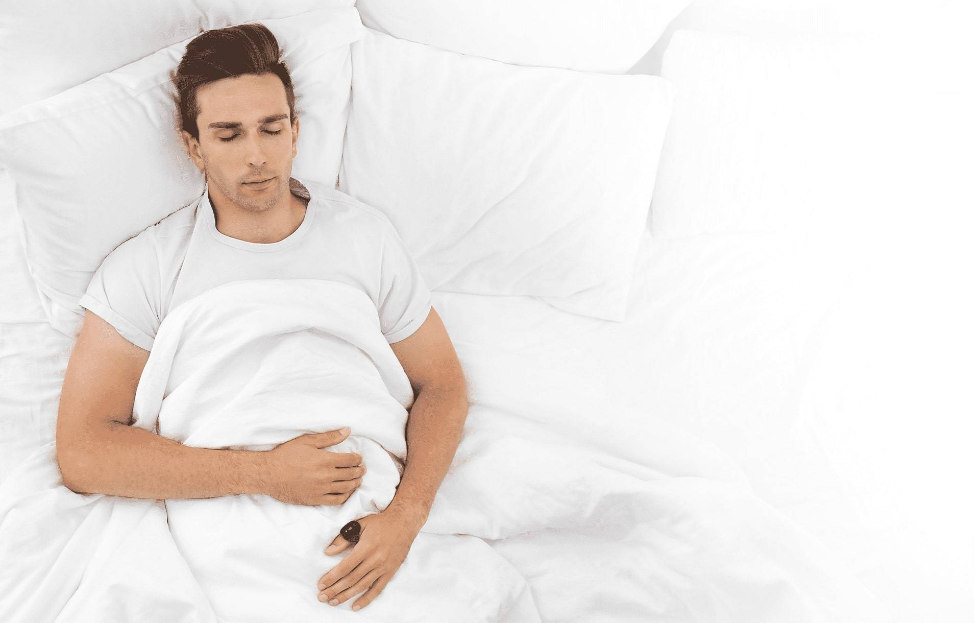 Man sleeping in a white pillow with O2 Ring