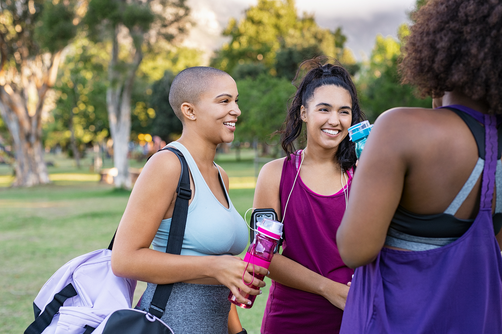 Group of multiethnic young women talking to each other after fitness exercising at park.