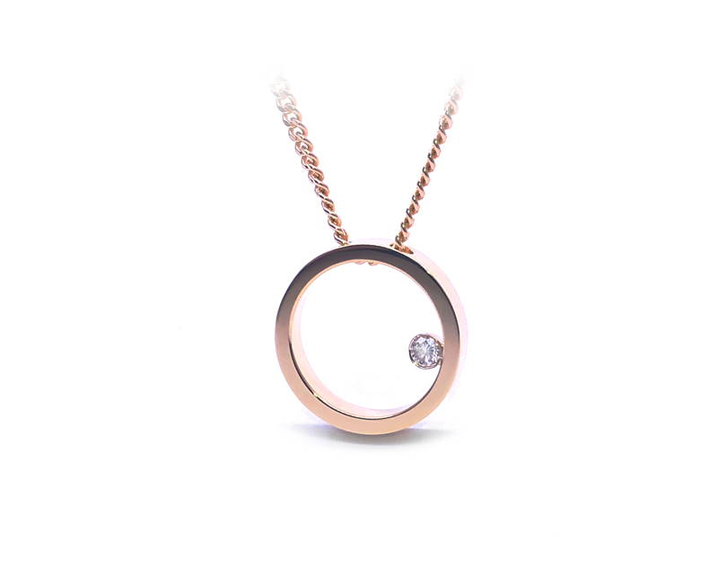 round pendant in yellow gold with small diamond inside