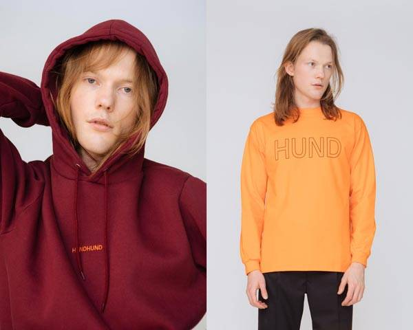Man wearing burgundy organic cotton hoodie with orange embroidered logo and man wearing organic cotton long sleeve t-shirt with black trousers