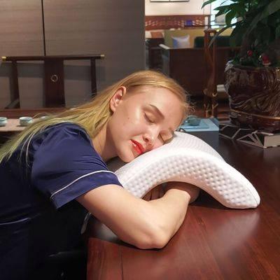 Femme utilisant un oreiller incurvé sur un bureau