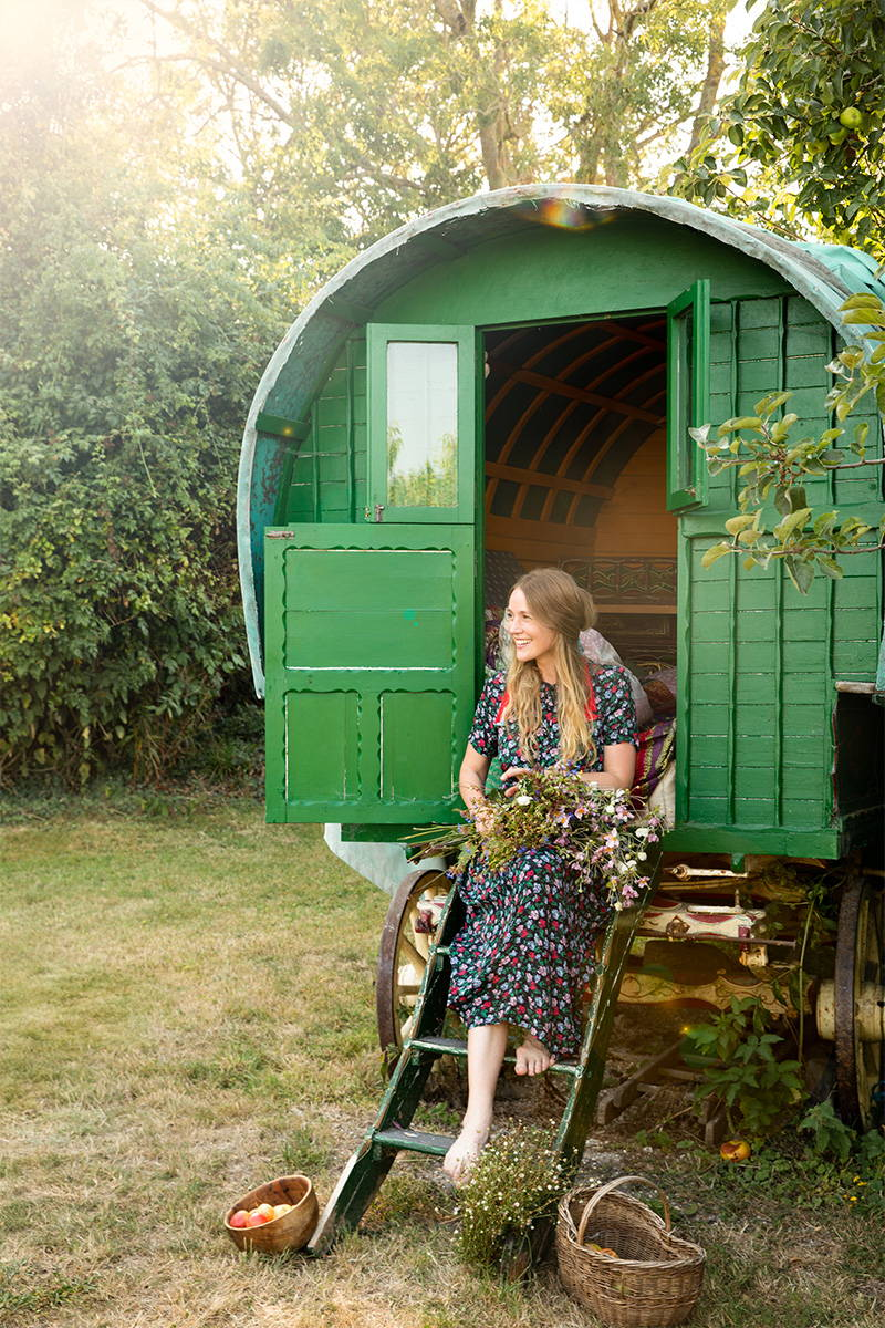 Tess Newall wears YOLKE's Juniper Dress and holds a bouquet of flowers whilst sitting on the stairs to her Gypsy Caravan