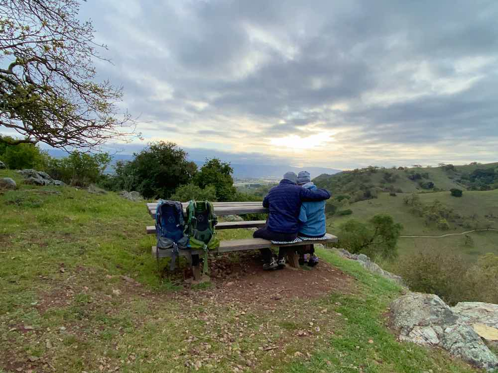 Couple snuggling at a picnic table overlooking green hills at Coyote Valley Open Space Preserve near San Jose