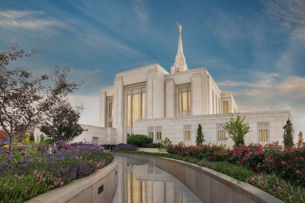 Angled photo of the Ogden Temple with reflective pavement.