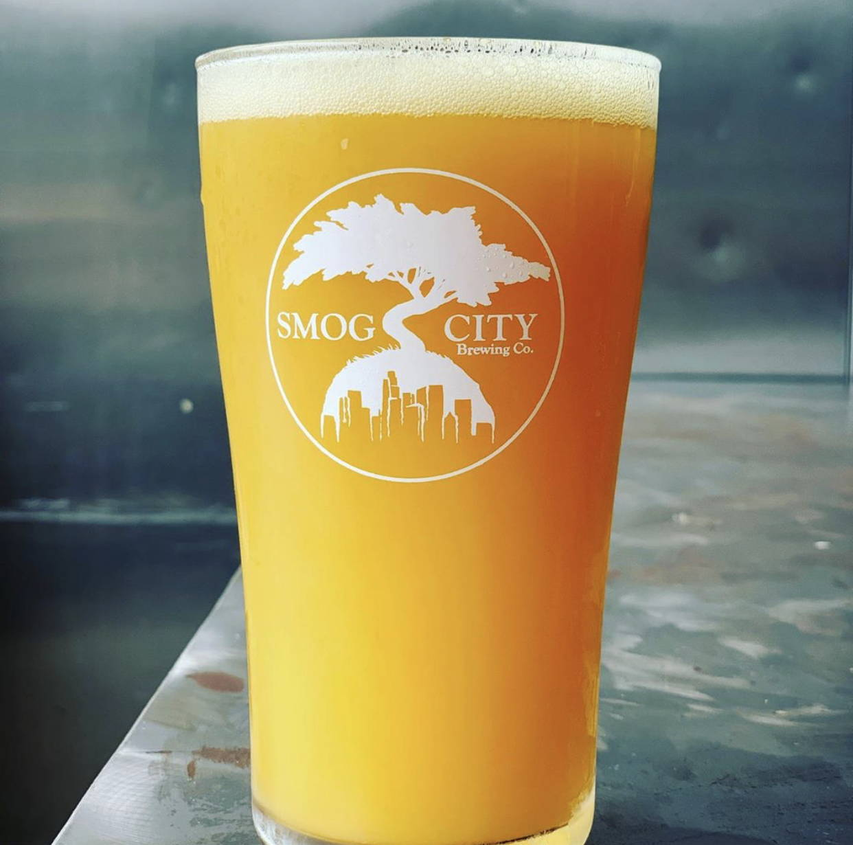 a pint glass of hazy ipa is seen with the smog city logo. it is sitting on a wooden bar.