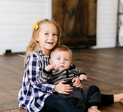 Older sister holds little brother and smiles at the camera