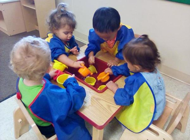 Found toddlers in smock at a low table with water in a built in bucket using plastic cups