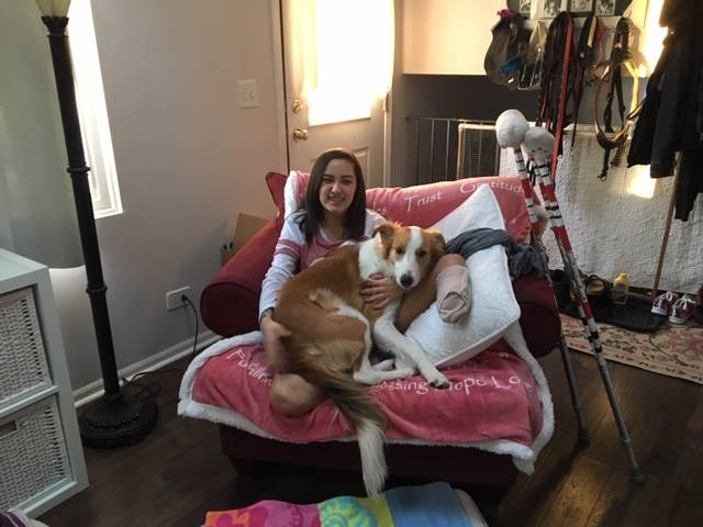 A photo of Marissa with her dog Koko Bean. Marissa is sitting in a chair at home recovering from amputation surgery, and Koko Bean is taking good care of her.