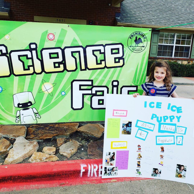 Photo of little girl with her project outside the school