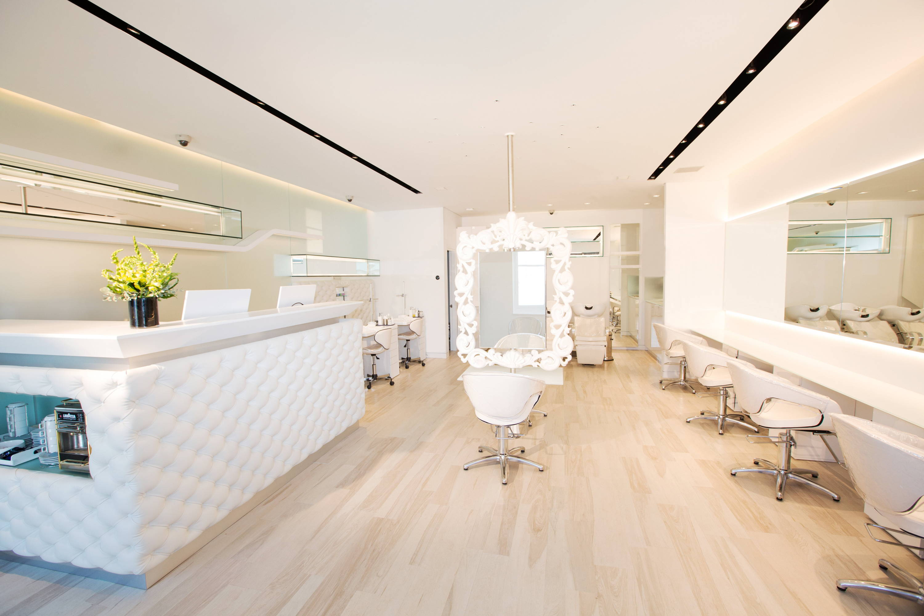 Warren Tricomi's East Hampton location with white check-in desk, long mirrors, and white salon chairs