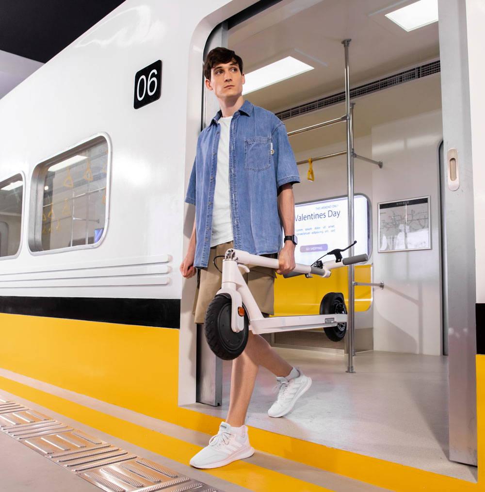 okai es20 neon man carrying escooter off train subway