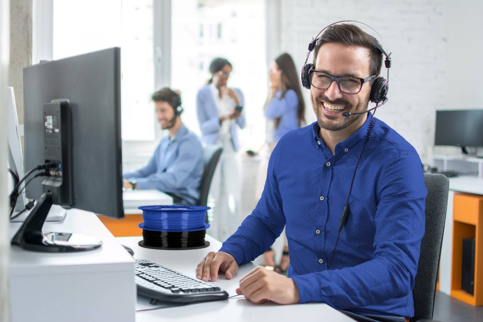 Image of Dremel DigiLab customer service representatives on a call with co-workers in background