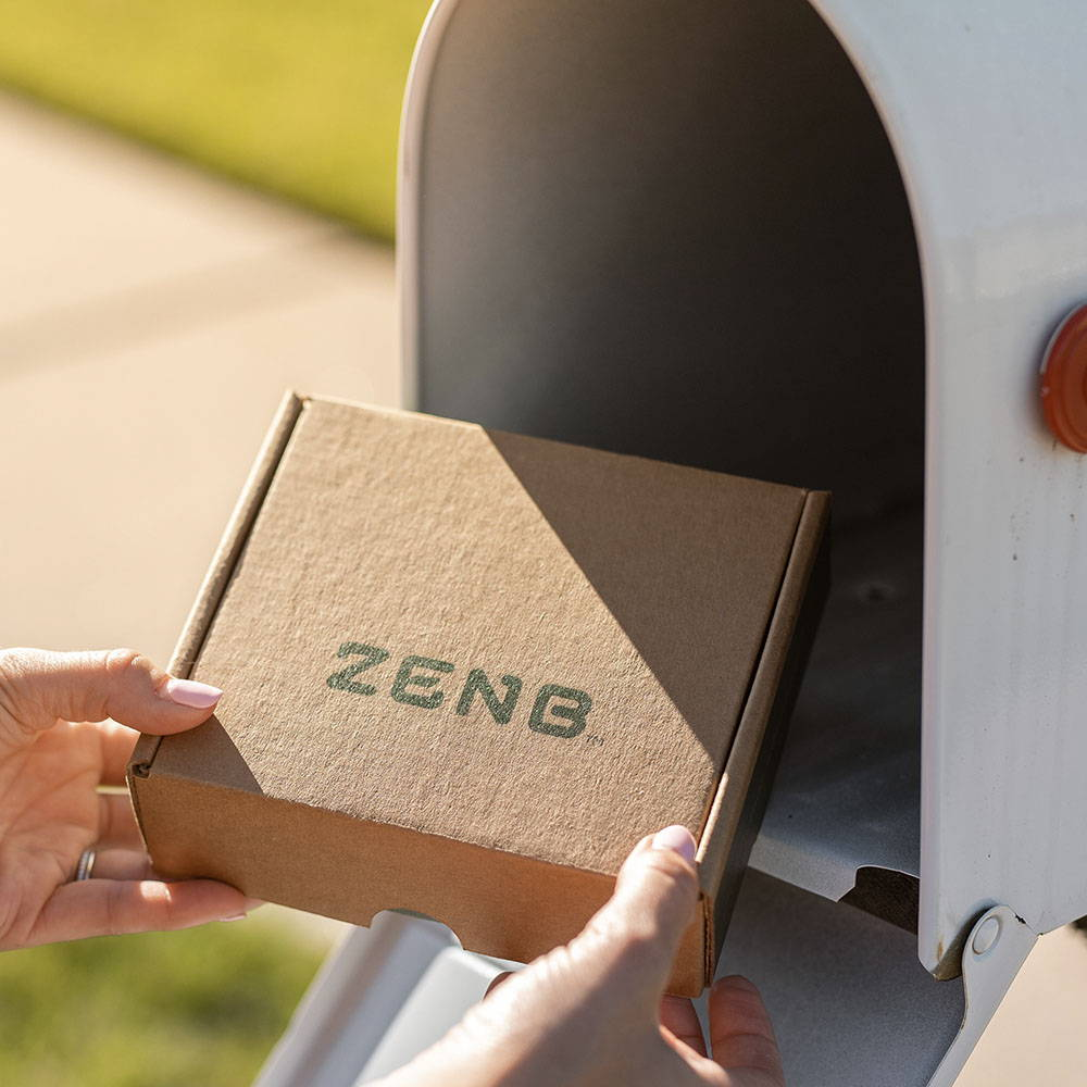 ZENB recycled shipper box is being pulled out of a white mailbox by a woman's hands on a sunny day