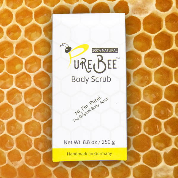 Hi, I'm Pure - the Original Body Scrub box in front of honey filled honey combs