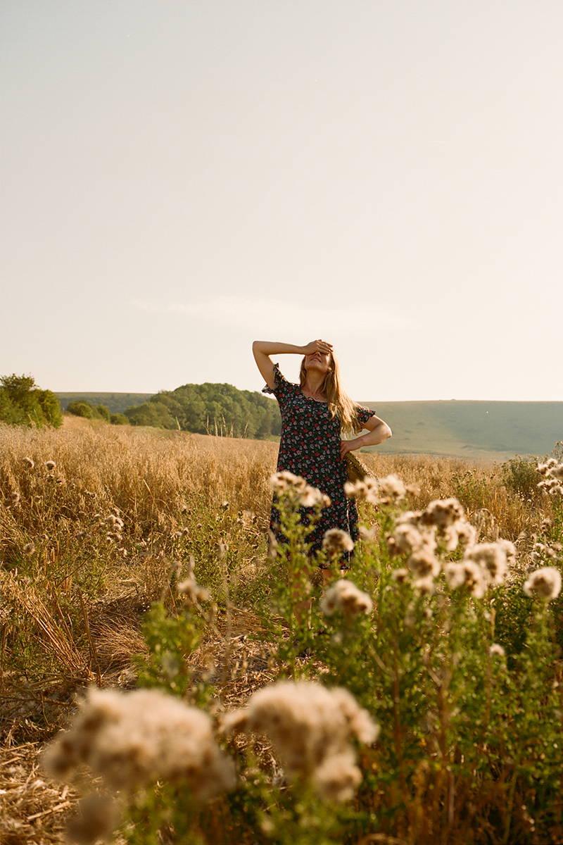 Tess Newall poses in a field of flowers wearing YOLKE Colette Dress