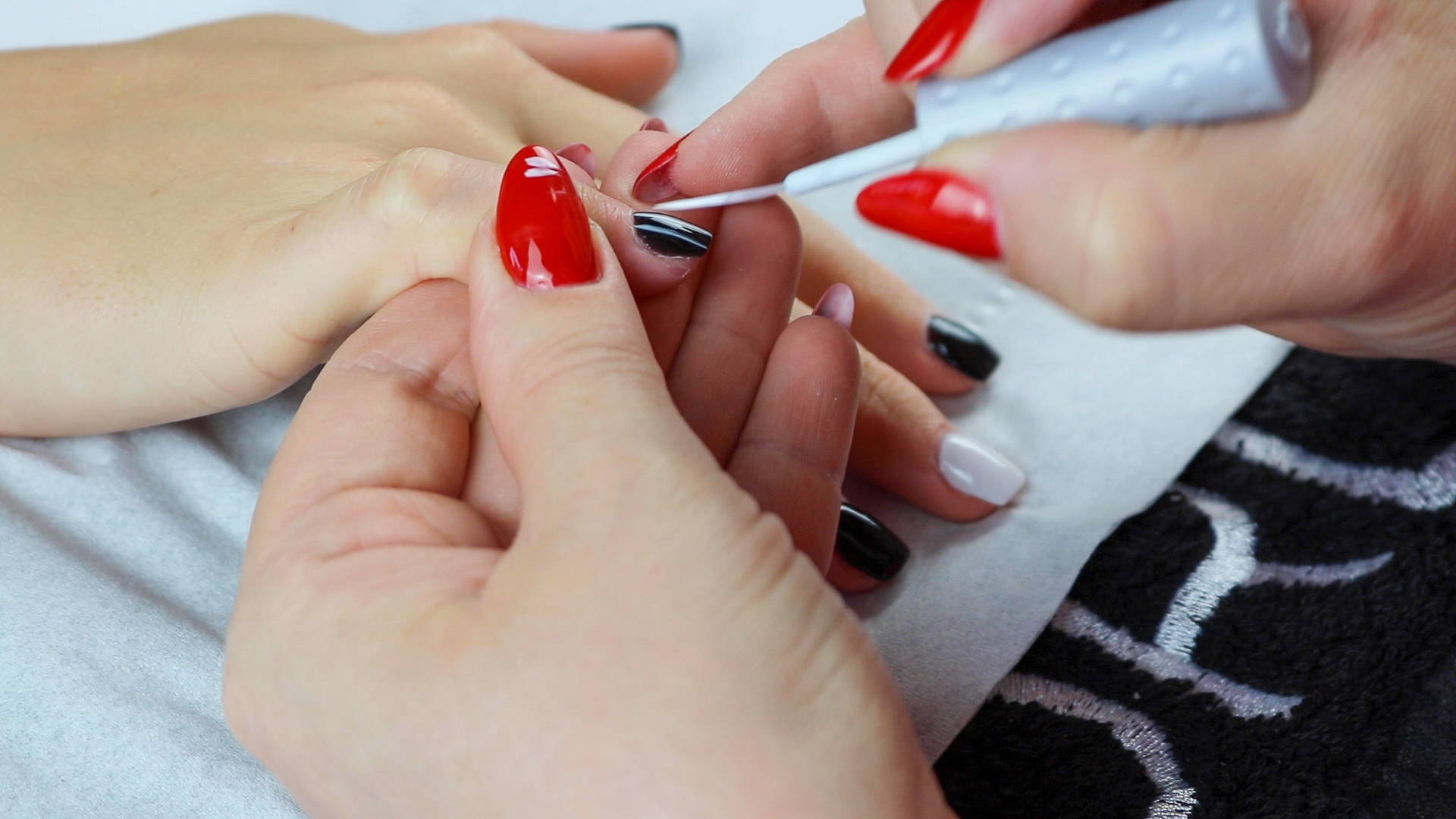 White stripes being painted onto black nails using ORLY White Tips to create Jack Skellington nails