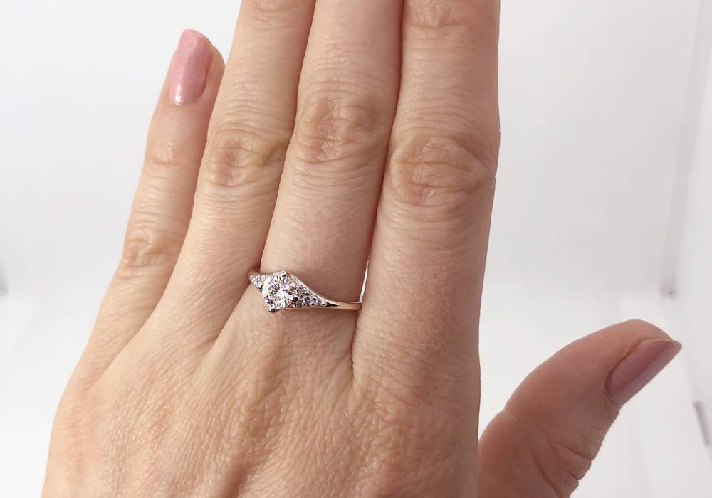 Bague de fiançailles avec diamant d'un demi carat au centre. Le diamant principal est entouré de 8 petits diamants.