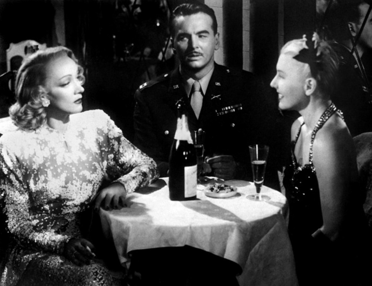 Marlene talking to a woman who is smiling in front of her while a soldier sits next to them at their table.