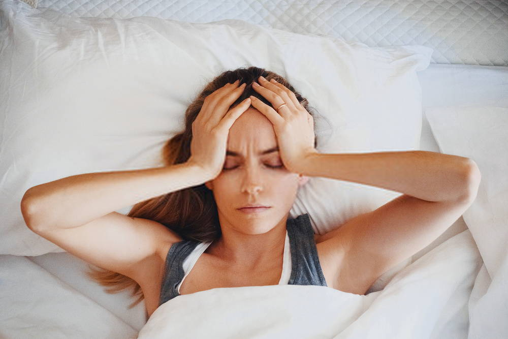 woman in bed with headache as she holds her head