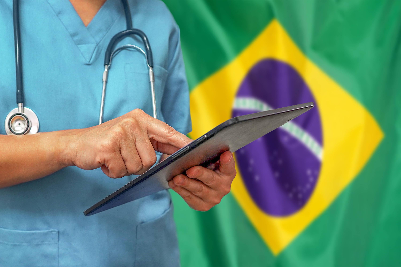 Médico diante de bandeira do Brasil