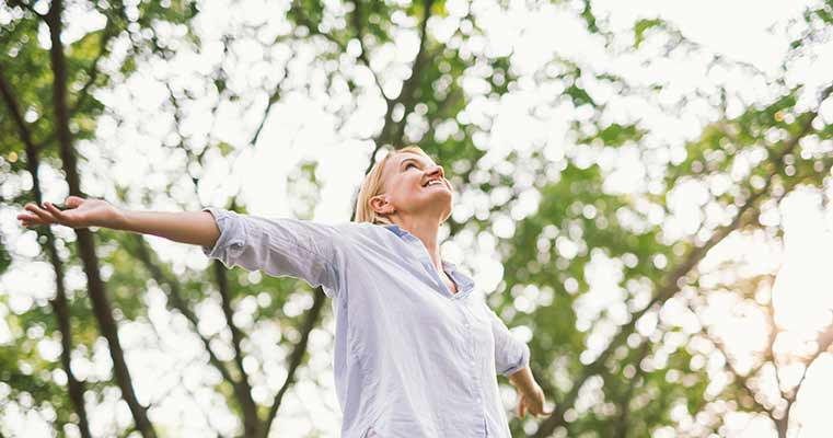 Happy woman surrounded by trees with arms outstretched