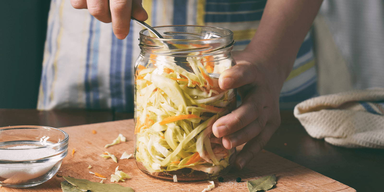 Woman scooping shredded cabbage out of a jar.