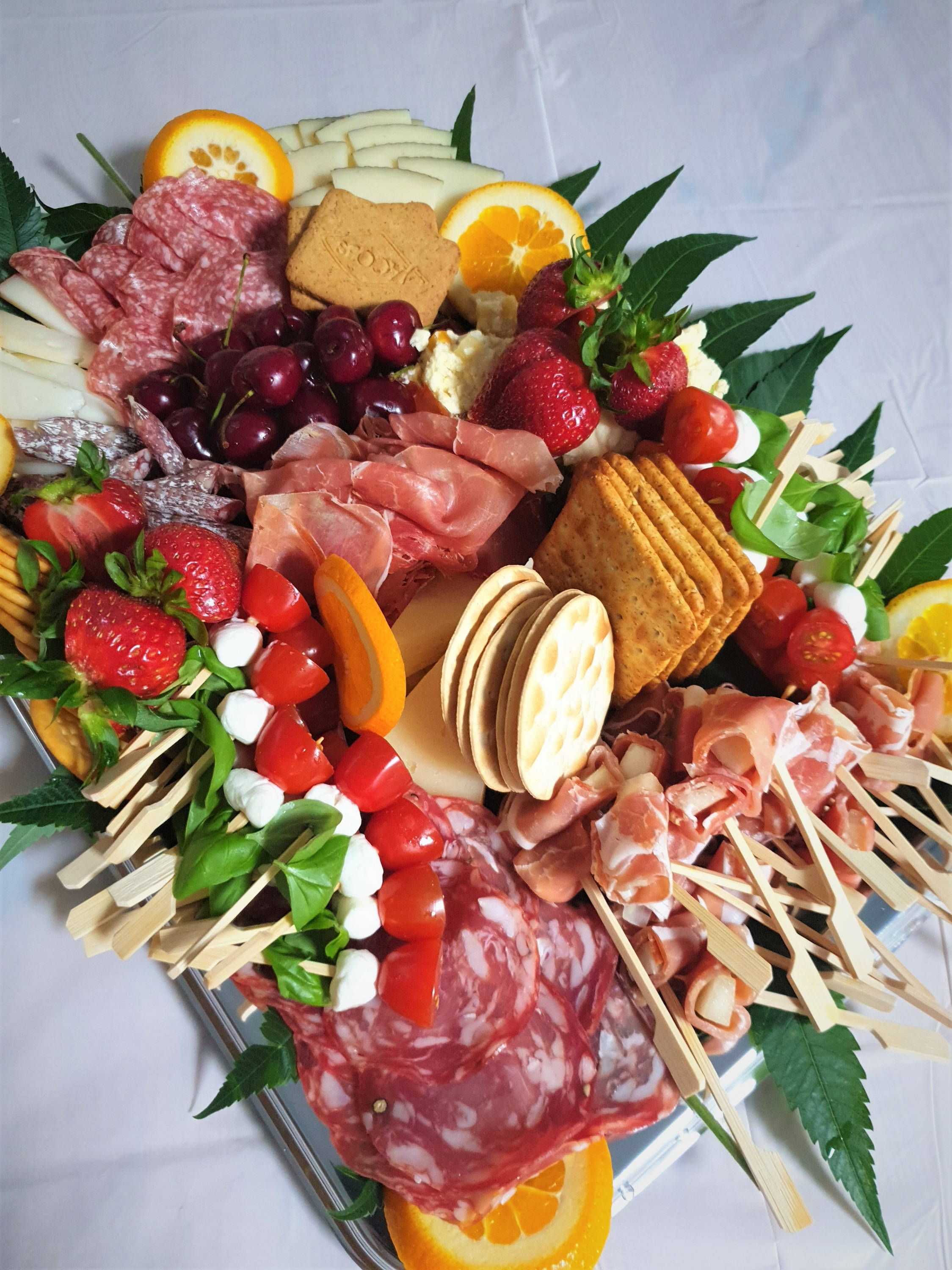Grazing board with cured meats, cheese, fresh and dry fruit, vegetables, grapes, olives, tomatoes, dips and crackers. Catering menu offered by Kidbay Parties, London Loves Catering.