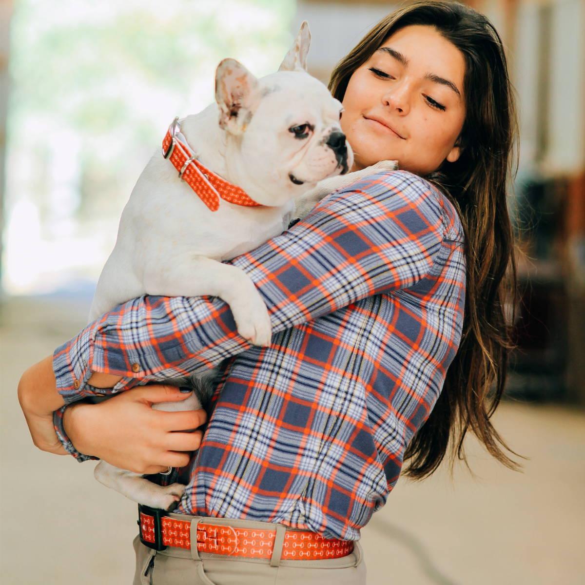 Women holding dog wearing an orange c4 belt
