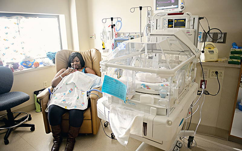 black nicu mother holding preemie baby next to window, for good NICU photography lighting