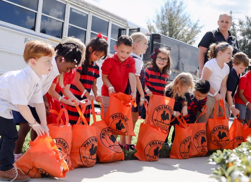 children holding bags of donations