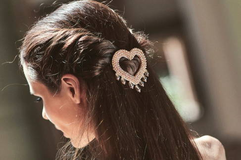 Close up view of CORA champagne crystal, heart shaped hair barrette worn with a braided half up-half down hair do.