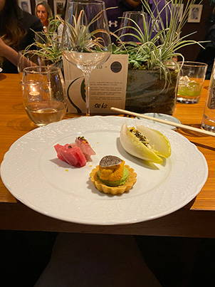A dinner plate with Crab Salad in endive shell, tart with uni, and sashimi