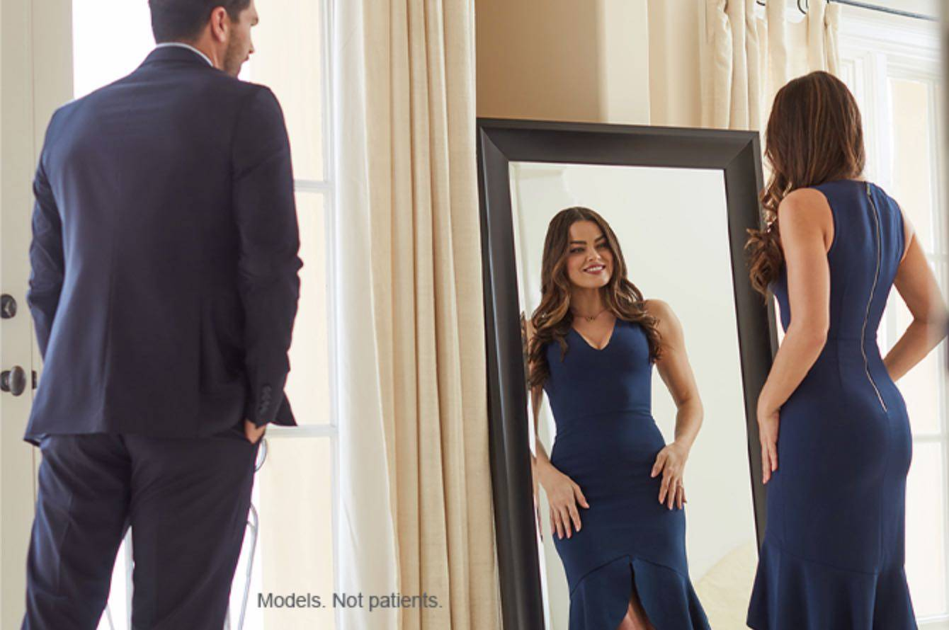 Woman In Slimming Blue Dress Looking In A Mirror