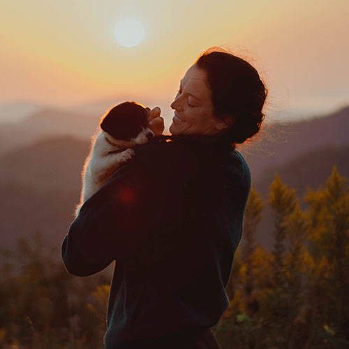 woman holding a border collie mix puppy