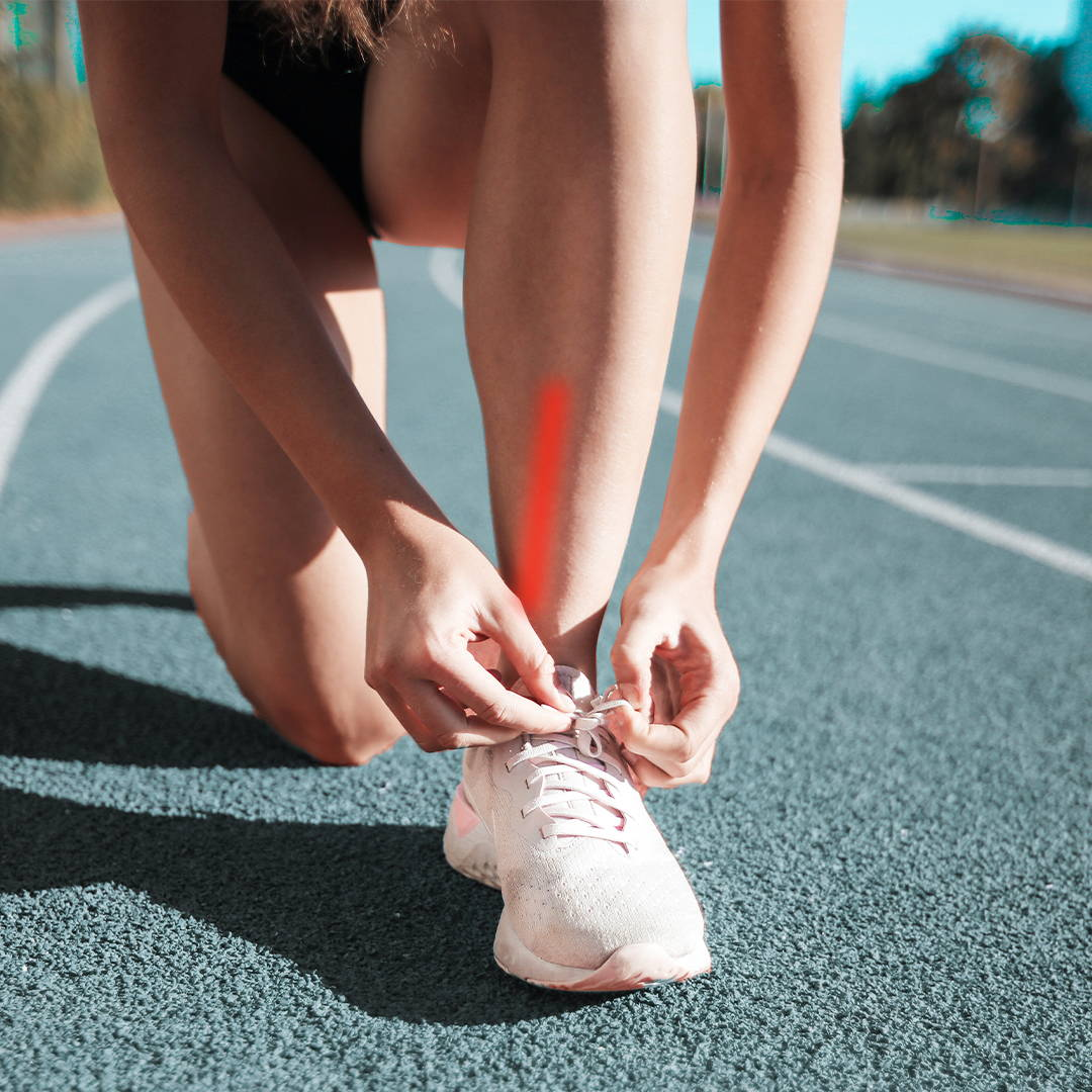 Girl tying a shoelace with shin splints shown in red