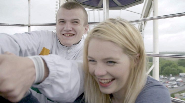 Two teenagers sit and laugh in a ferris wheel compartment.