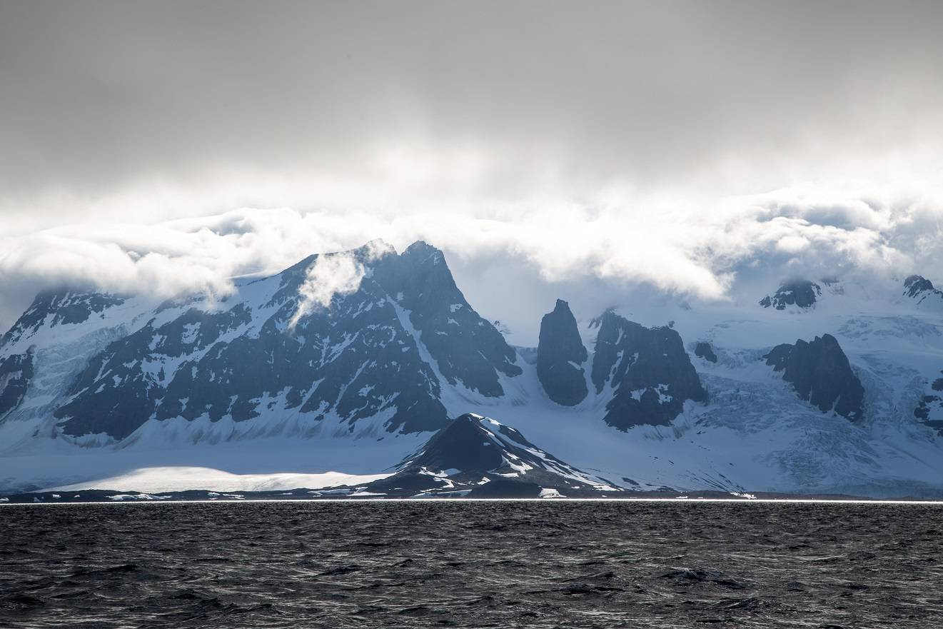 Mountains of Svalbard with clouds rolling across top of them seen from sea
