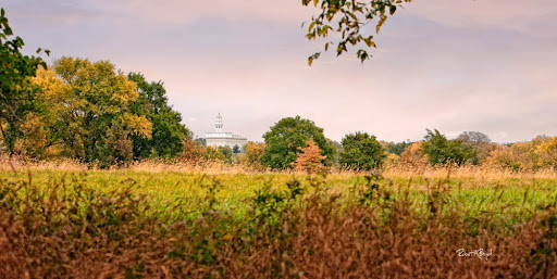 Distant photo of the Nauvoo Temple from across a field.