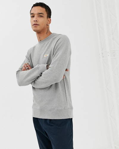 Man wearing grey organic cotton nudie jeans sweatshirt with blue chino trousers