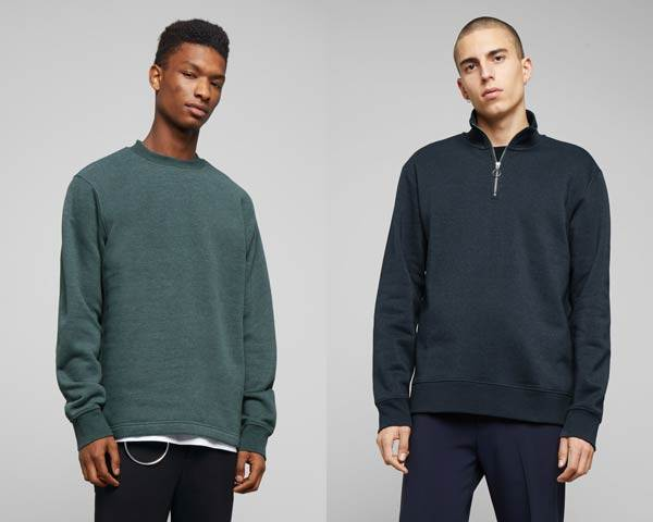 Man wearing dark navy blue quarter zip organic cotton jumper with navy trousers and man wearing soft green sweatshirt with black jeans from sustainable fashion brand Weekday