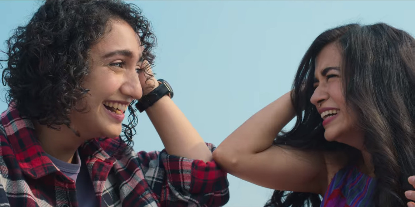 Muskaan and Tarasha laughing together while reclingin on a table.