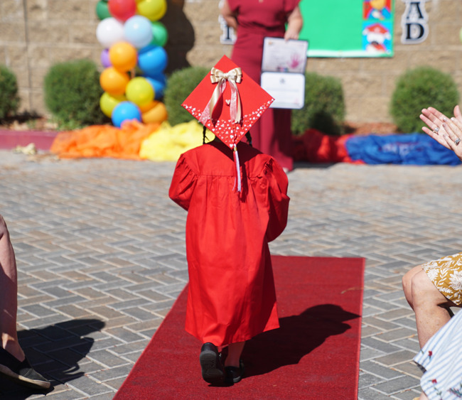 back of student walking down the graduation aisle wearing a red gown and decorated cap