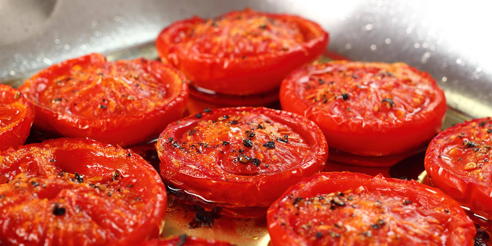 Roasted Tomatoes in a pan with oil.