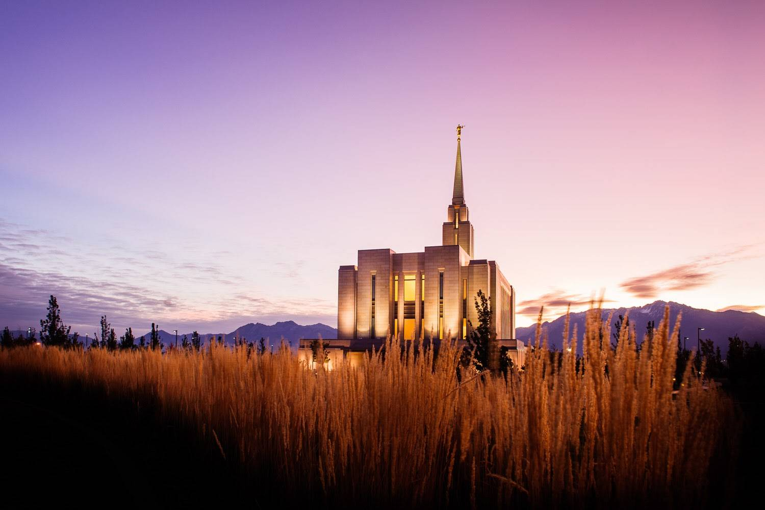 Panoramic photo of the Oquirrh Mountain Utah LDS Temple against a purple sky and surrounded by a field.