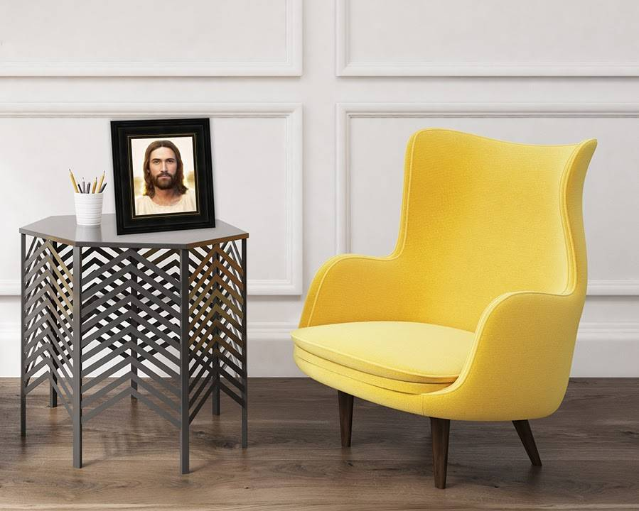 A small art portrait of Christ sitting on stylish coffee table next to a yellow chair.