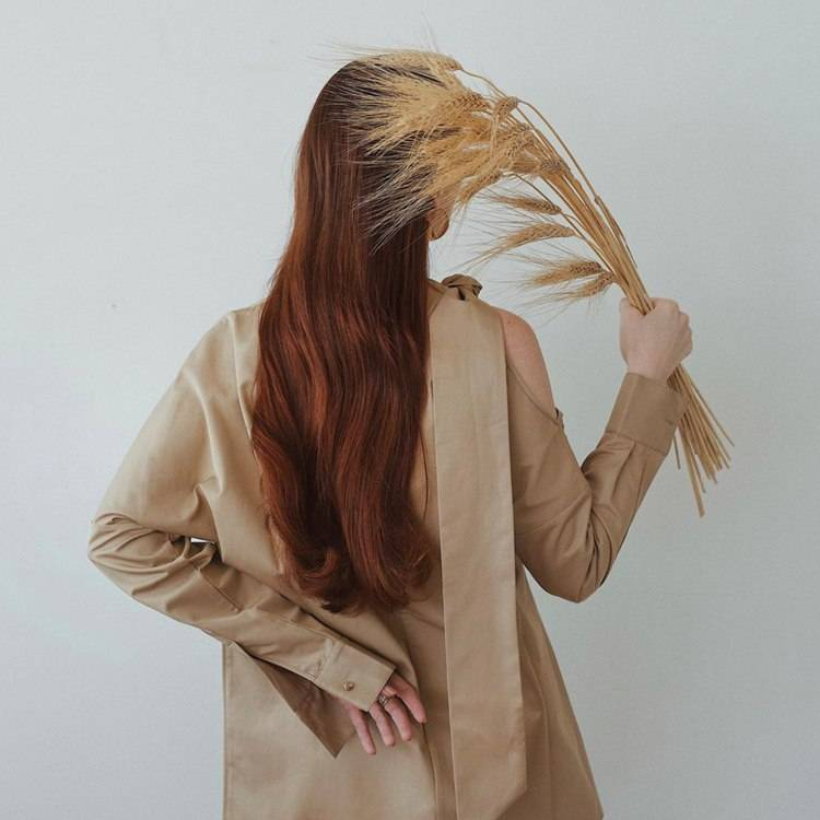 a woman is holding a bunch of barley